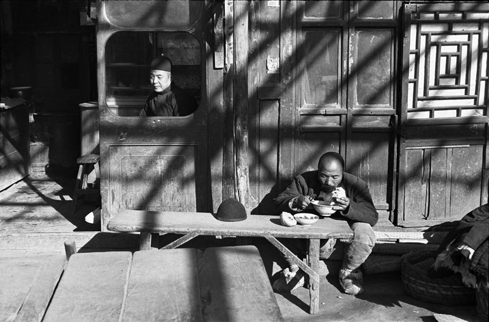 亨利.卡蒂埃.布列松  | 坐在食肆窗內的跑堂或店主,苦力在簷下用餐 北平,1948年12月    © Fondation Henri Cartier-Bresson / Magnum Photos
